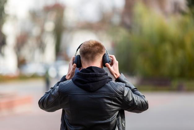 Junger mann der hinteren ansicht, der musik auf kopfhörern hört