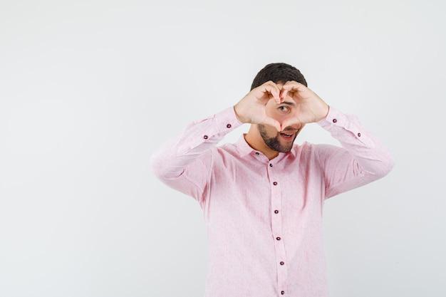 Junger mann, der hitzegeste im rosa hemd zeigt und nett aussieht