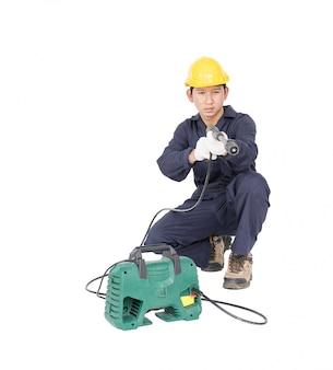 Junger mann, der hochdruckwasserwerfer sitzt und hält