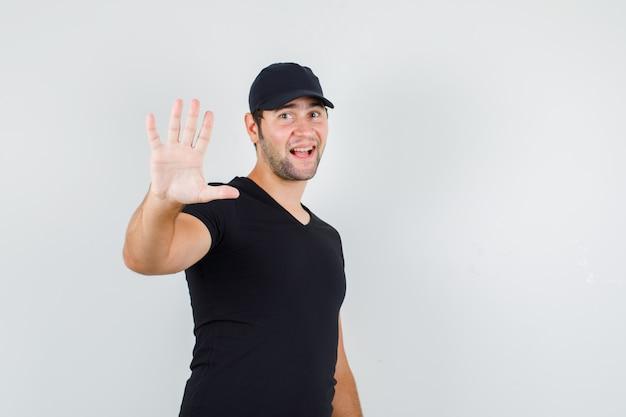 Junger mann, der höflich stoppgeste im schwarzen t-shirt zeigt