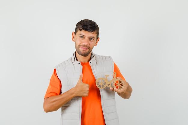 Junger mann, der hölzernes spielzeugfahrrad hält und daumen oben im t-shirt zeigt