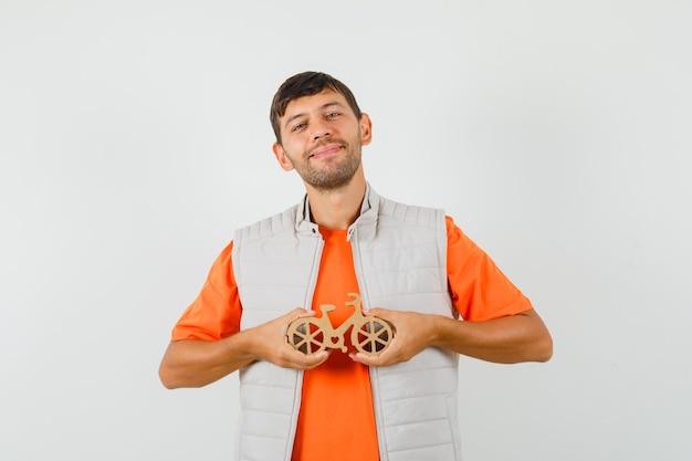 Junger mann, der hölzernes spielzeugfahrrad im t-shirt hält