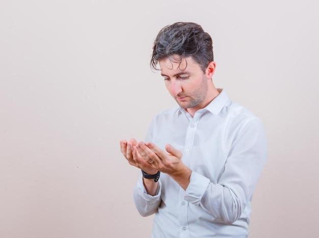 Junger mann, der hohle hände in betender geste im weißen hemd hält und hoffnungsvoll aussieht