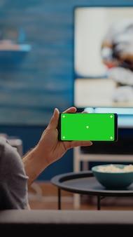 Junger mann, der horizontalen grünen bildschirm auf smartphone beobachtet