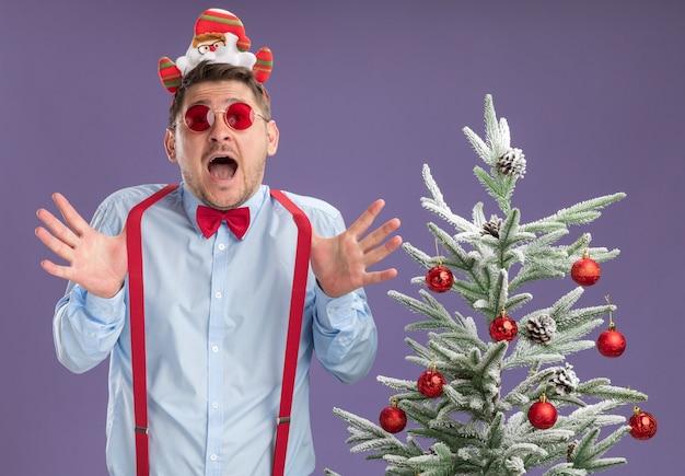 Junger mann, der hosenträgerfliege im rand mit weihnachtsmann und roter brille trägt, die neben weihnachtsbaum stehen, überrascht und erstaunt mit weit geöffnetem mund über lila wand