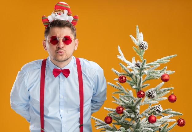 Junger mann, der hosenträgerfliege im rand mit weihnachtsmann und roter brille trägt, die neben weihnachtsbaum stehen und kamera nah mit ernstem gesicht über orange hintergrund betrachten