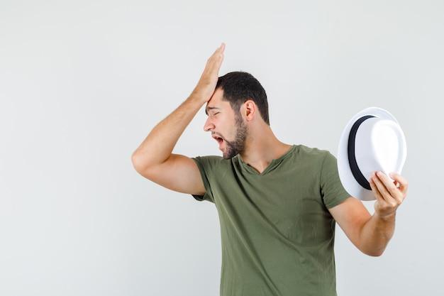 Junger mann, der hut mit hand auf stirn im grünen t-shirt hält und vergesslich schaut
