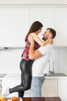Junger mann, der ihre freundin in der küche trägt