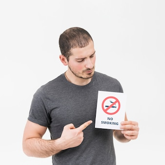 Junger mann, der ihren finger in richtung zum nichtraucherzeichen lokalisiert auf weißem hintergrund zeigt