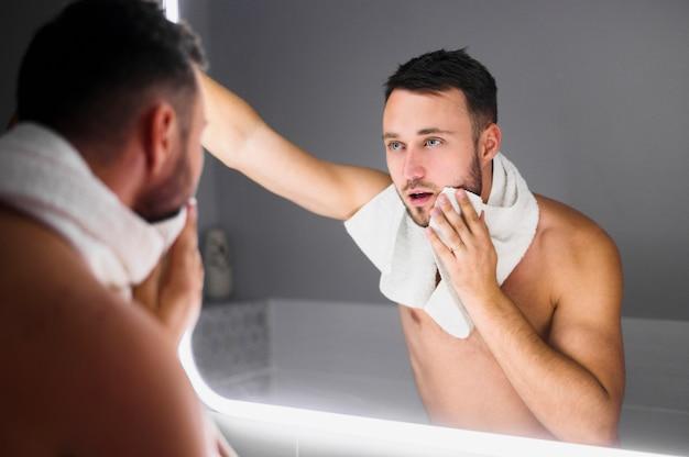 Junger mann, der im badezimmerspiegel schaut
