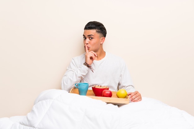 Junger mann, der im bett tut ruhegeste frühstückt