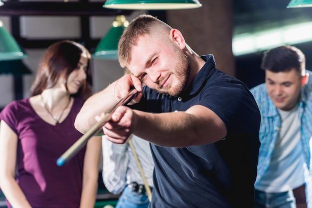 Junger mann, der im billard spielt. posieren in der nähe des tisches mit einem stichwort in den händen