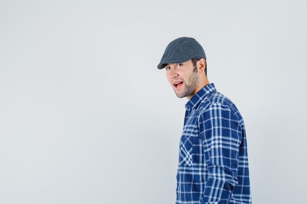 Junger mann, der im blauen hemd, in der mütze und im fröhlichen blick beiseite schaut.