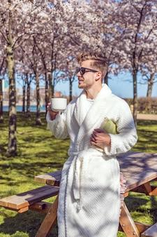 Junger mann, der im blühenden garten des frühlings sich entspannt und kaffee von der tasse trinkt