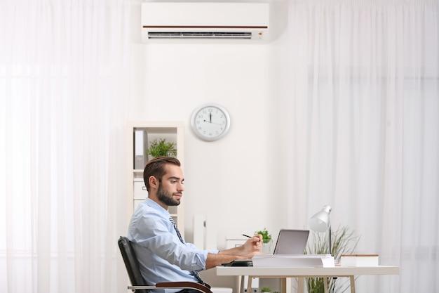Junger mann, der im büro mit klimaanlage arbeitet