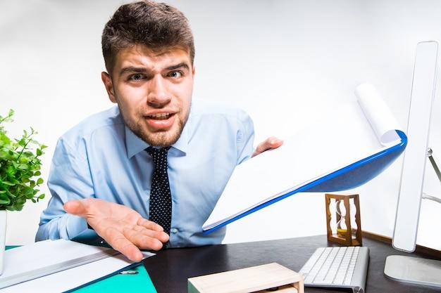 Junger mann, der im büro verärgert und wütend wird