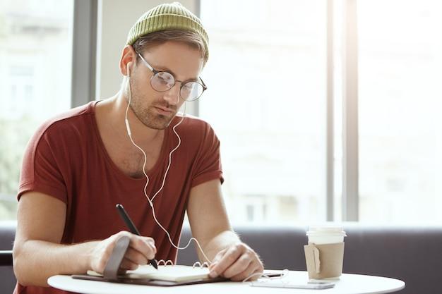 Junger mann, der im café sitzt, das musik hört