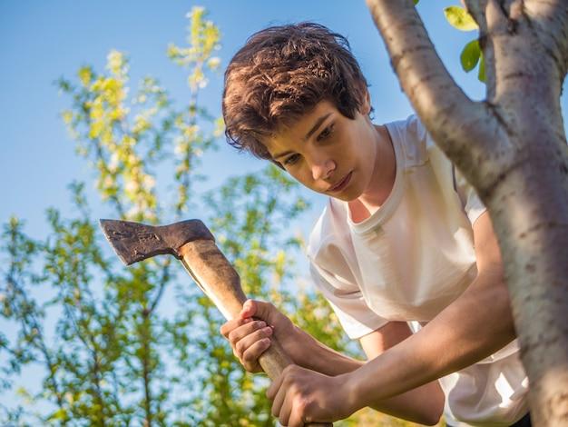 Junger mann, der im garten mit axt nahe dem baum arbeitet