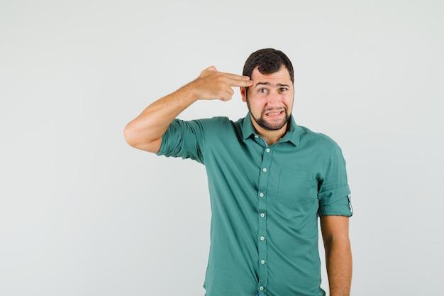 Junger mann, der im grünen hemd eine pistolengeste an seinem kopf zeigt und gelangweilt aussieht. vorderansicht.