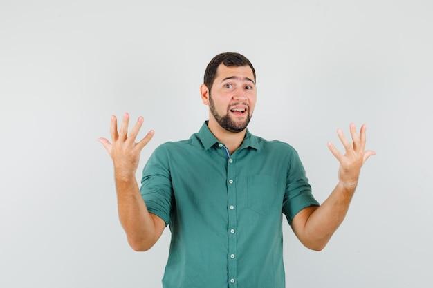 Junger mann, der im grünen hemd hilflos zeigt und verzweifelt aussieht. vorderansicht.