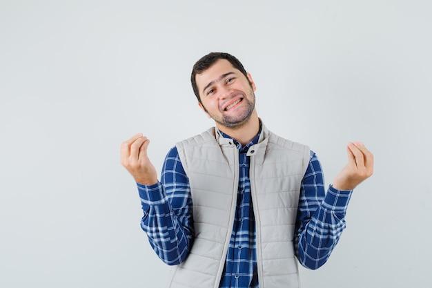 Junger mann, der im hemd, in der ärmellosen jacke meditiert und glücklich schaut. vorderansicht.