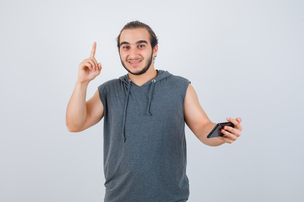 Junger mann, der im kapuzen-t-shirt oben zeigt und glückliche vorderansicht schaut.