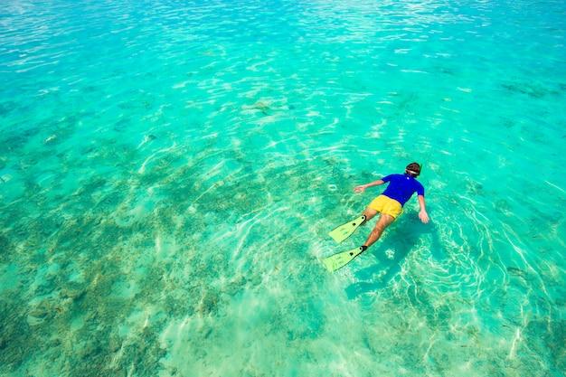 Junger mann, der im klaren tropischen türkiswasser schnorchelt