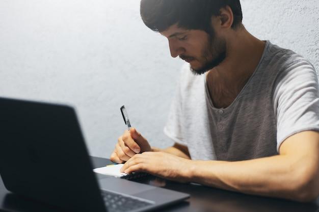 Junger mann, der im notizbuch schreibt und mit laptop arbeitet.