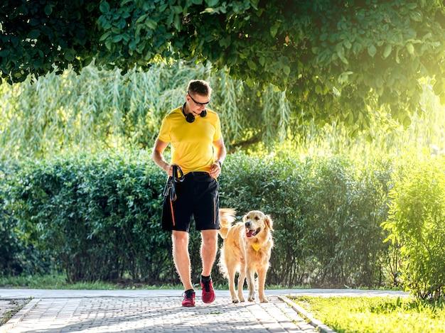 Junger mann, der im park mit goldenem retrieverhund joggt