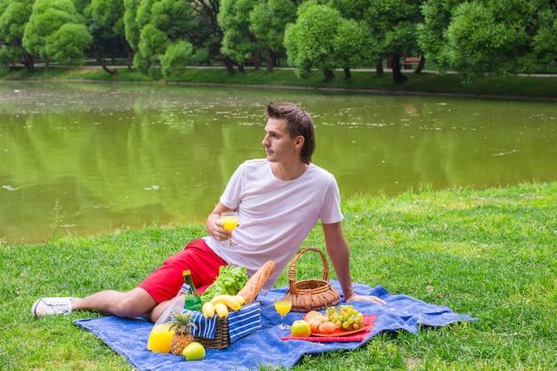 Junger mann, der im park picknickt und sich entspannt