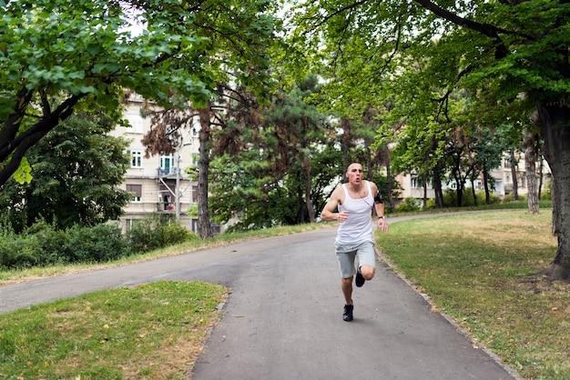 Junger mann, der im park rüttelt gesunder lebensstil.