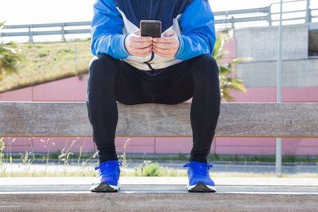 Junger mann, der im park sitzt und sein handy konsultiert, um sport zu treiben