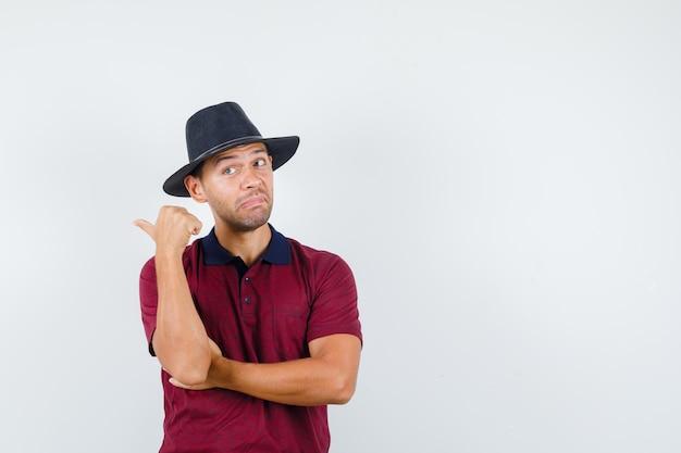 Junger mann, der im roten hemd, im schwarzen hut zurück zeigt und verwirrt schaut, vorderansicht. platz für text