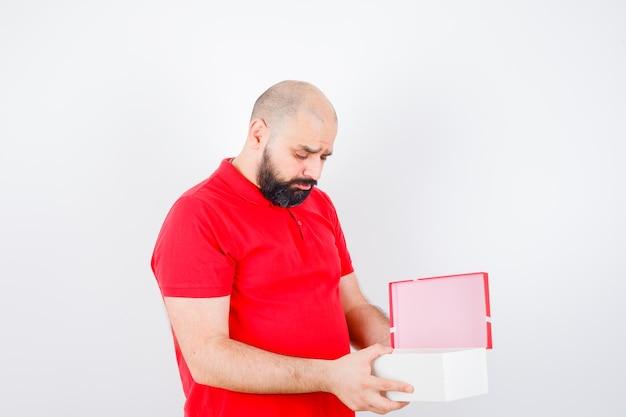 Junger mann, der im roten hemd in die kiste schaut und emotional aussieht.
