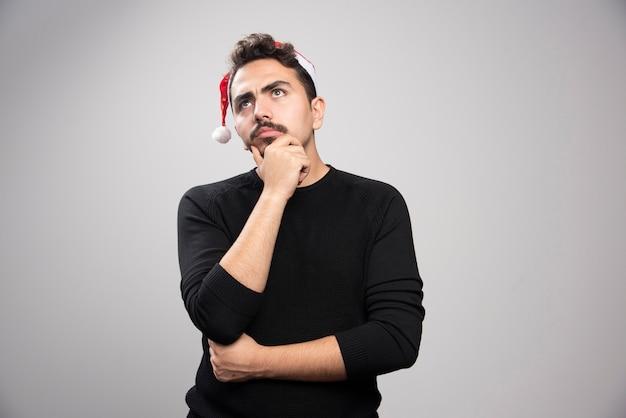 Junger mann, der im roten hut des weihnachtsmanns denkend aufwirft.