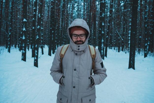Junger mann, der im schneebedeckten wald des winters steht