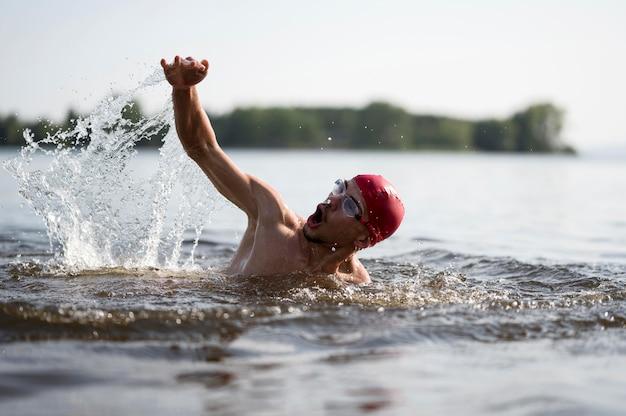 Junger mann, der im see schwimmt