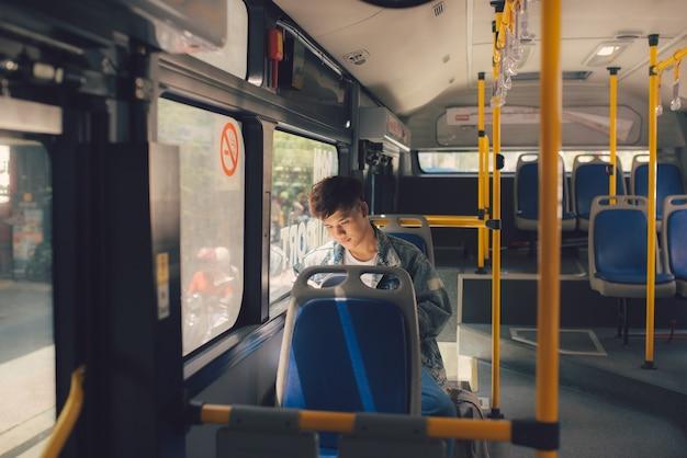 Junger mann, der im stadtbus sitzt und ein buch liest.