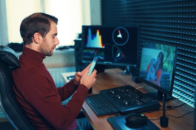 Junger mann, der im studio mit einem smartphone und computer arbeitet. kaukasischer freiberufler, der handy hält, das an filmmaterial, video, design arbeitet.