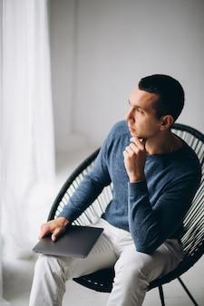 Junger mann, der im stuhl sitzt und laptop verwendet