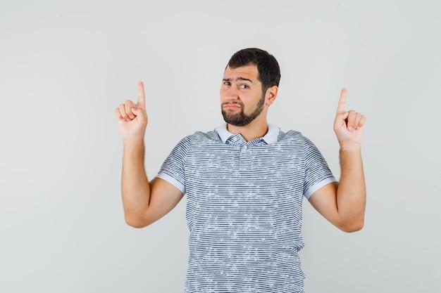 Junger mann, der im t-shirt nach oben zeigt und hoffnungslos aussieht, vorderansicht.