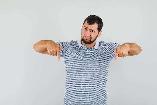 Junger mann, der im t-shirt nach unten zeigt und verzweifelt aussieht, vorderansicht.