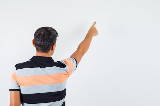 Junger mann, der im t-shirt weg zeigt und konzentriert schaut