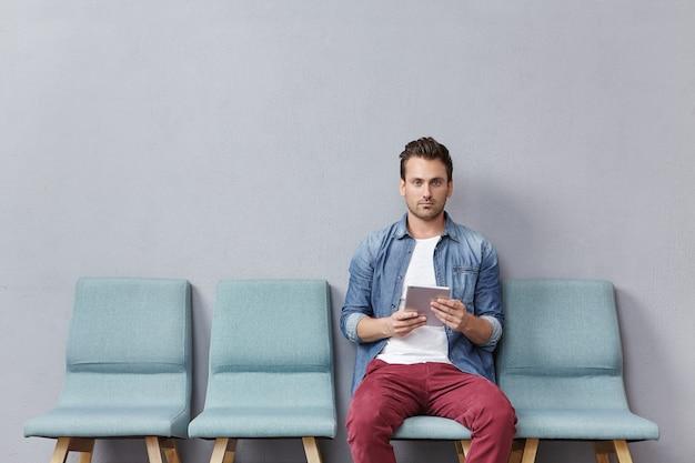 Junger mann, der im wartezimmer sitzt tablette hält
