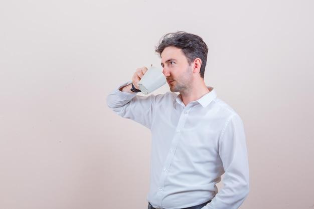 Junger mann, der im weißen hemd aromatischen tee trinkt und nachdenklich aussieht