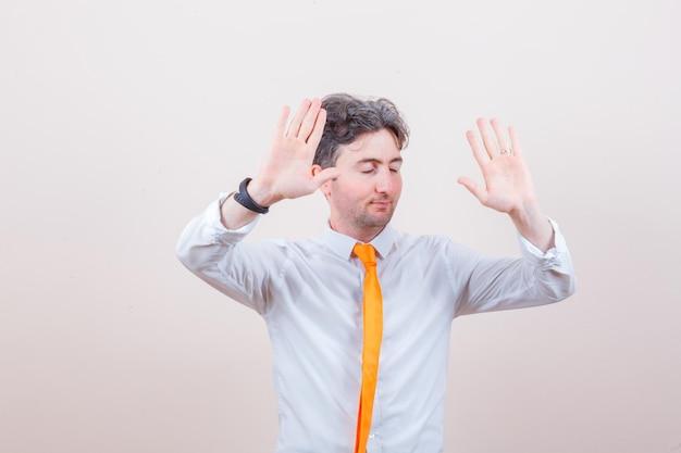 Junger mann, der im weißen hemd eine stopp-geste zeigt und erschöpft aussieht