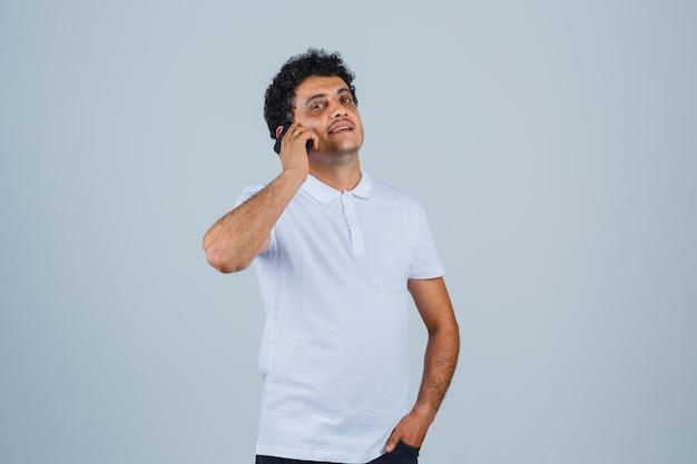 Junger mann, der im weißen t-shirt am handy spricht und stolz aussieht. vorderansicht.