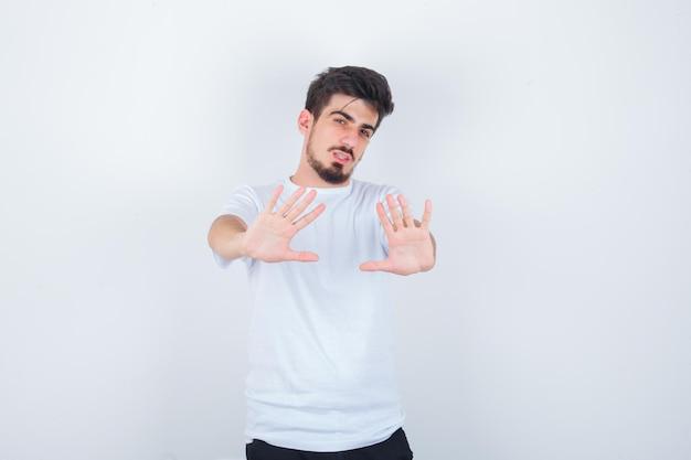 Junger mann, der im weißen t-shirt eine stopp-geste zeigt und selbstbewusst aussieht