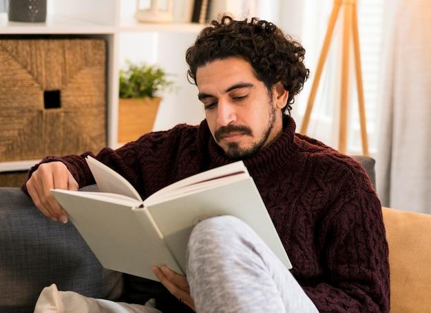 Junger mann, der im wohnzimmer liest