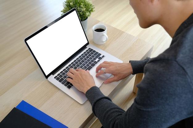 Junger mann, der im wohnzimmer zu hause sitzt und laptop-computer benutzt.